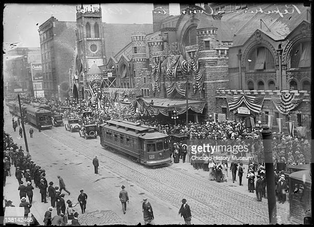 Coliseum building decorated with flags during the 1920 Republican National Convention with the sidewalk and street in front of the building crowded...