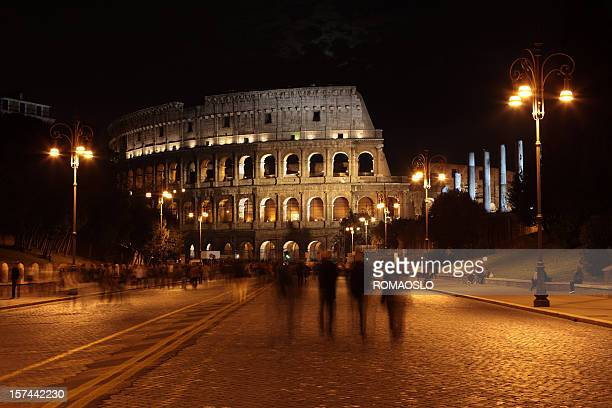 Coliseum by night and people walking