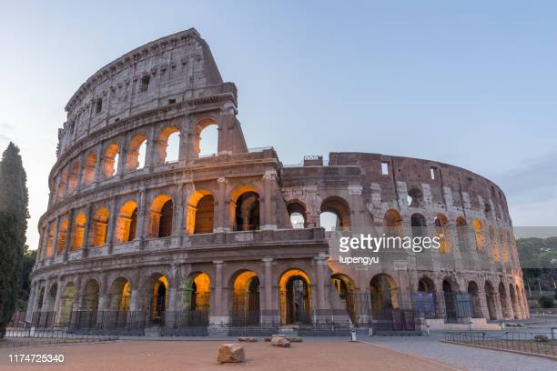 coliseum in rome at dusk - colosseum stock pictures, royalty-free photos & images
