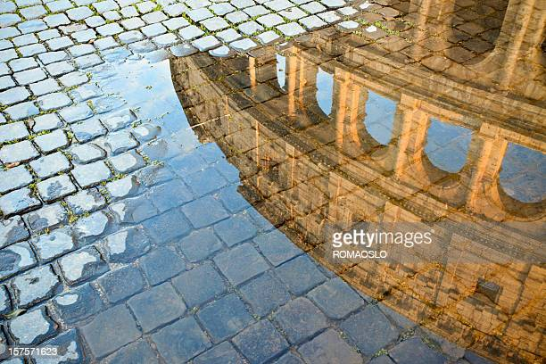 coliseum reflected in a puddle, roma italy - coliseum rome stock photos and pictures