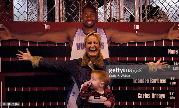 Lizzy Murray of Denver compares her arm span to that of a cut out of Nuggets player Nene while carring her 10monthold son Adam The pair were visiting...