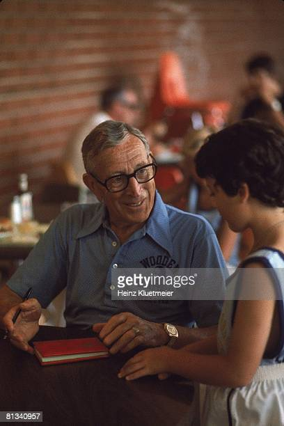 Coll Basketball Portrait of former UCLA coach John Wooden at his basketball camp signing autograph 1/1/1975