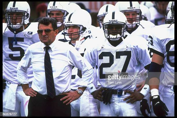 Portrait of Penn St. Coach Joe Paterno on sidelines w. Players during game vs Indiana.