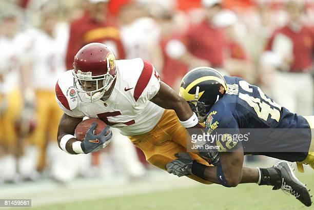 Coll Football Rose Bowl USC's Reggie Bush in action vs Michigan's Lawrence Reid Pasadena CA 1/1/2004
