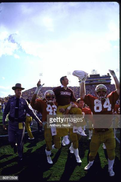 View of Florida St. Coach Bobby Bowden being carried off field on players shoulders after winning game vs Florida.