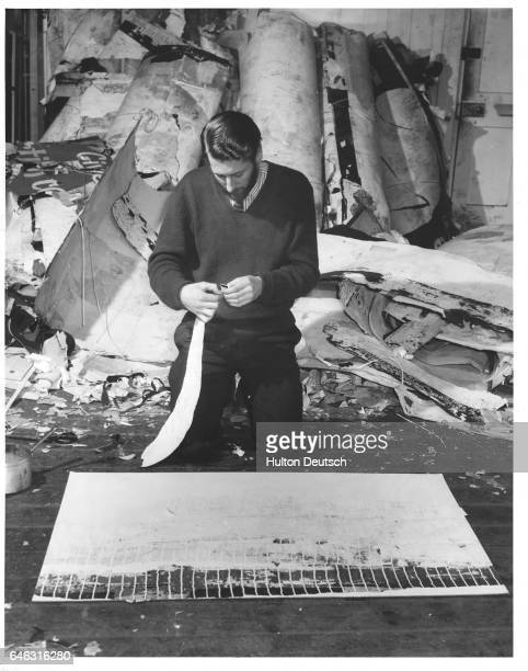 Collage artist Gwyther Irwin kneels in front of one of his works in progress a collage of poster strips he tears from the rolls of posters at his back
