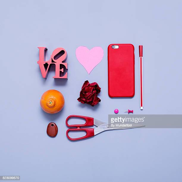 Collage of different red, orange and pink objects on a blue background seen from above