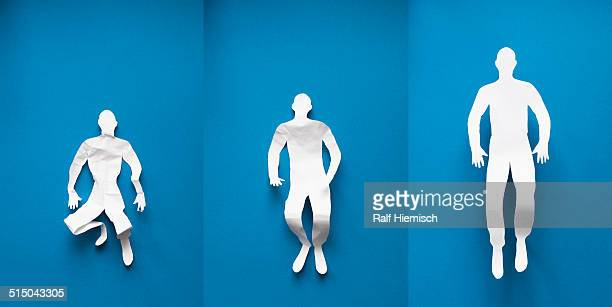 Collage of paper man showing stages of life over blue background