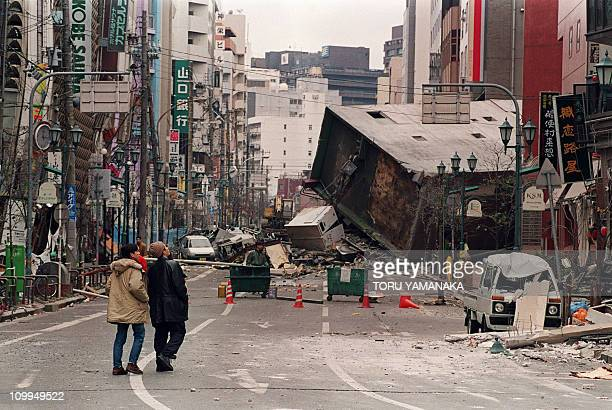 A collapsed building blocks the main street of central Kobe on January 18 1995 following the massive earthquake that rocked western Japan on January...