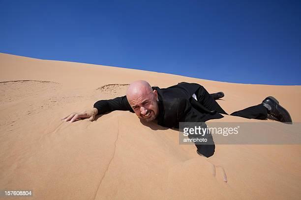 Eingeklappt Geschäftsmann in der Wüste