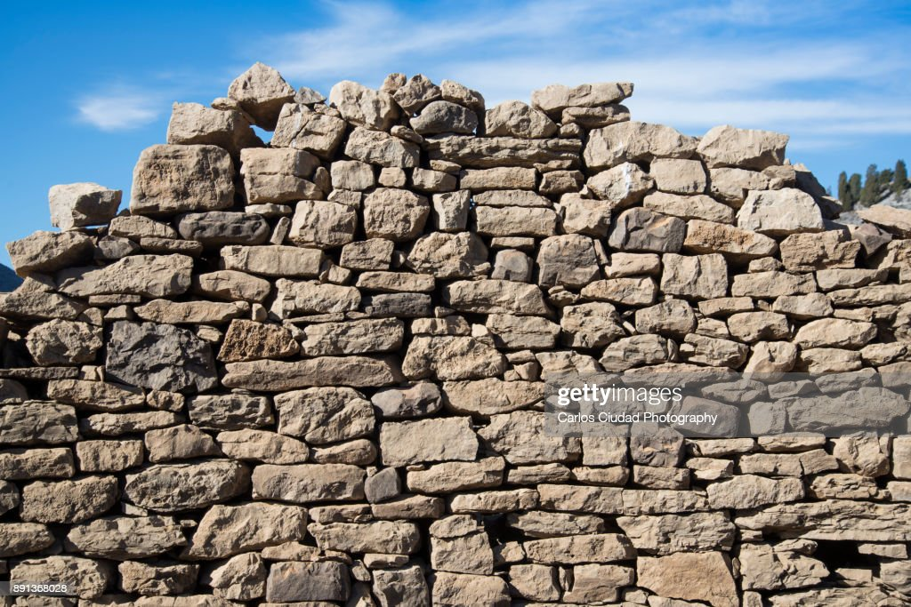 Collapsed dry stone wall against blue sky : Foto de stock