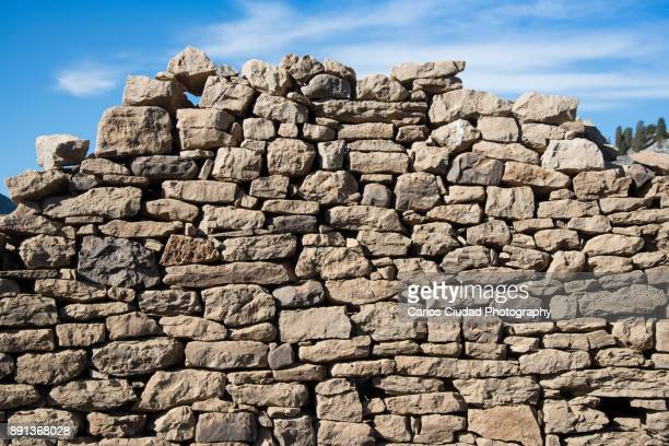 Collapsed dry stone wall against blue sky