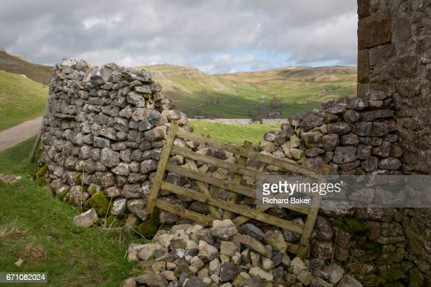 Collapsed dry stone wall and a leaning protective gate on farmland near Gordale Scar, on 12th April 2017, at Malham, in the Yorkshire Dales, England.
