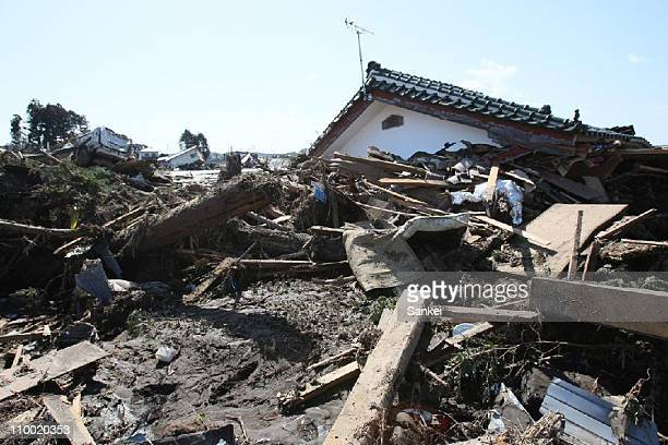 A collapsed house and debris caused by the tsunami are seen on March 12 2011 in Minamisoma Fukushima Japan An earthquake measuring 89 on the Richter...
