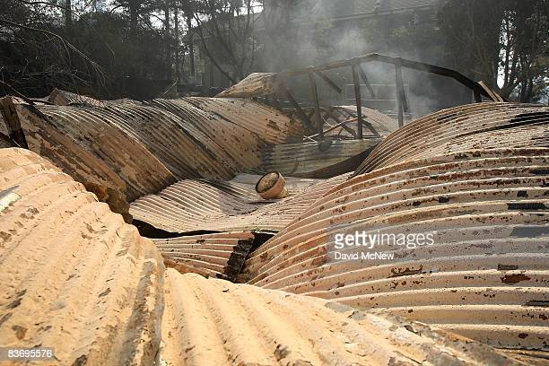 A collapsed roof lies atop the smoldering remains of a building at Westmont College destroyed by the Tea Fire on November 14 2008 in Montecito...