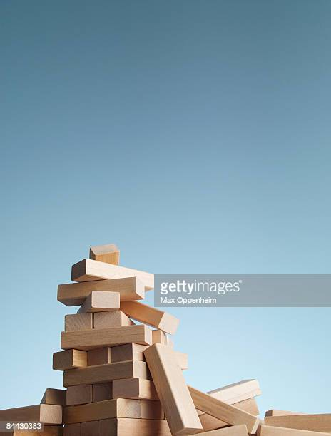Collapsed tower of blocks against a blue sky