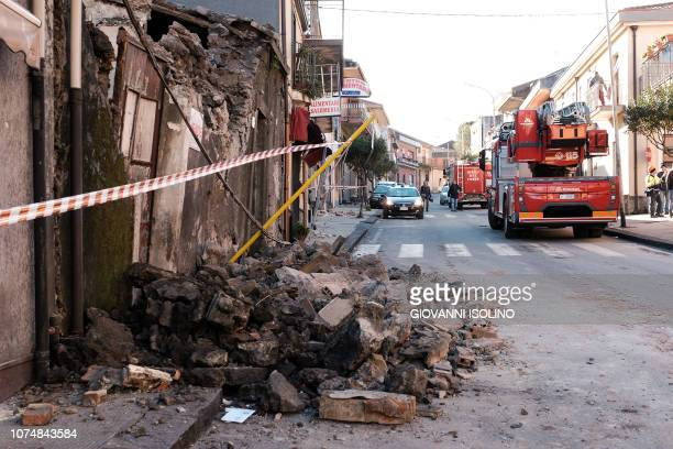 Collapsed wall is pictured as vehicles of first responders and firefighters are parked on a main road in Zafferana Etnea near Catania on December 26...