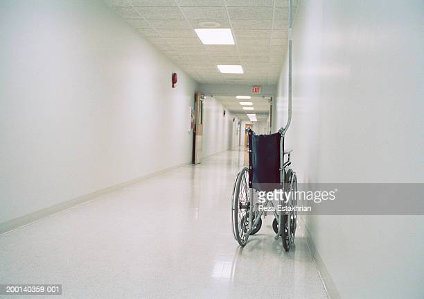 collapsible wheelchair in empty corridor of hospital - mort concepts photos et images de collection