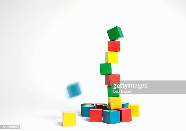 collapsing tower of colored building blocks - collapsing stock pictures, royalty-free photos & images