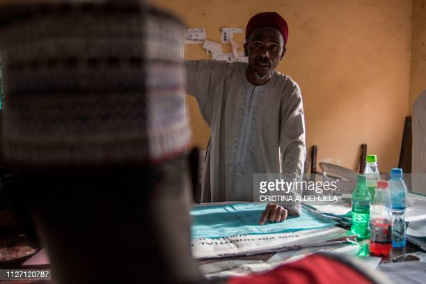 A collation officer along with INEC members gather at a Local Government Area of South Kaduna on February 24 as they recount the election results...