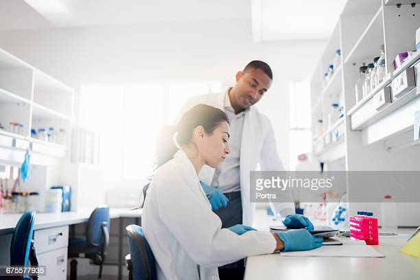 Colleague discussing with scientist at laboratory