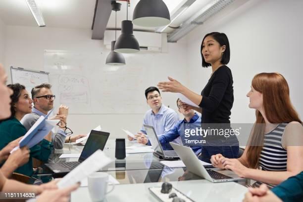 プレゼンテーションスピーチを行う同僚。ベルリンのオフィスで会議室を開催。 - セールストーク ストックフォトと画像