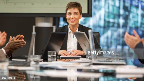 colleagues applauding smiling female ceo - executive director stock pictures, royalty-free photos & images