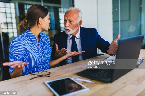 colleagues arguing at workplace - bossy stock pictures, royalty-free photos & images