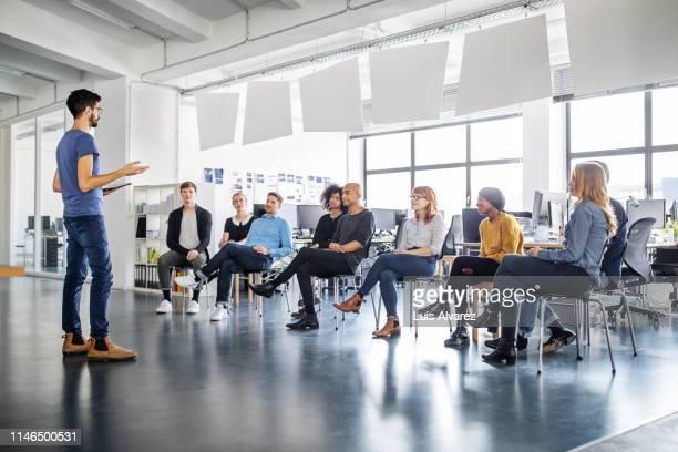 colleagues at an office meeting - teilnehmen stock-fotos und bilder