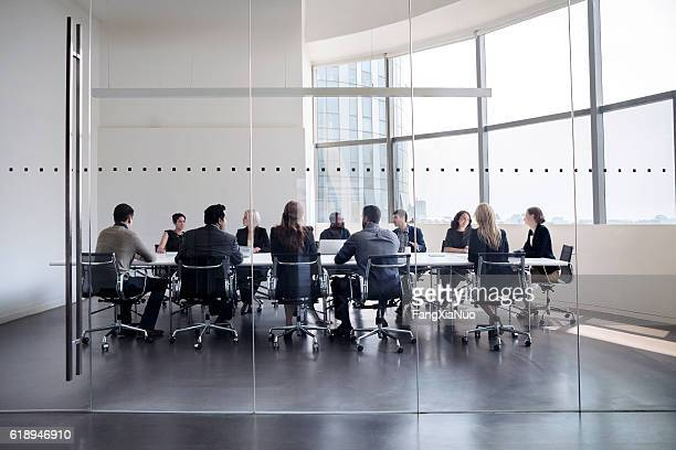 colleagues at business meeting in conference room - beslissingen stockfoto's en -beelden