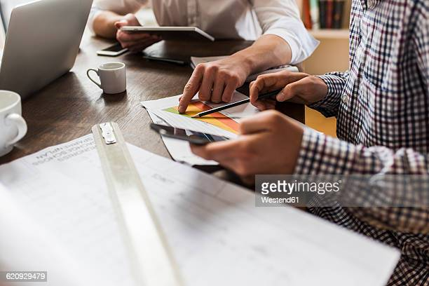 Colleagues at desk with smartphone, diagram and construction plan