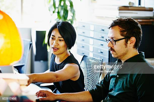 colleagues at workstation working on project - leanintogether stock pictures, royalty-free photos & images