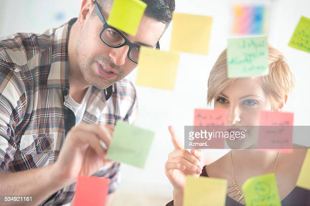 Colleagues attaching sticky notes to a glass partition