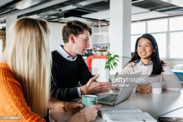 colleagues brainstorming at desk - three people stock pictures, royalty-free photos & images