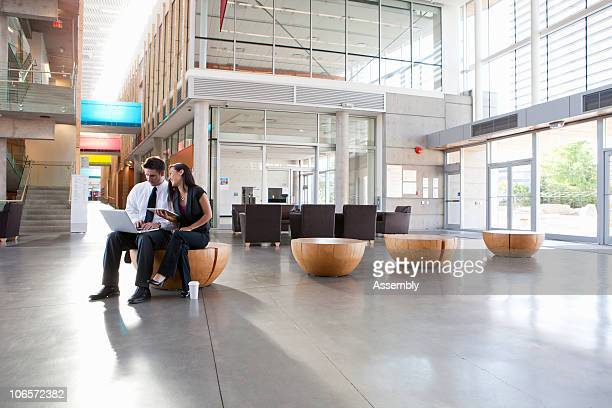 colleagues casual meeting in office lobby - hot desking photos et images de collection