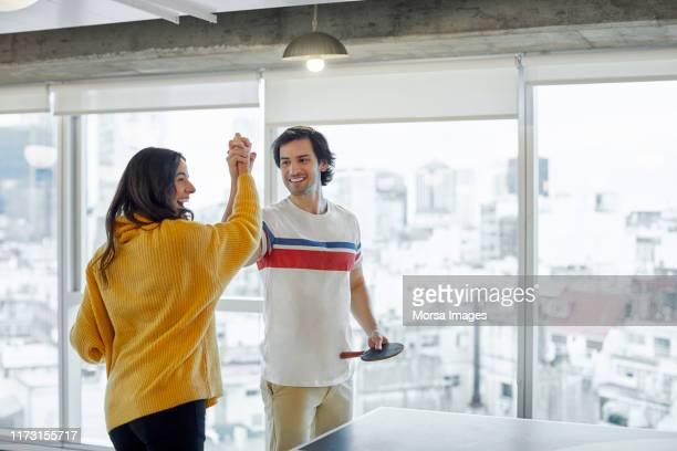 colleghi che tifano mentre giocano a ping pong - doppio foto e immagini stock