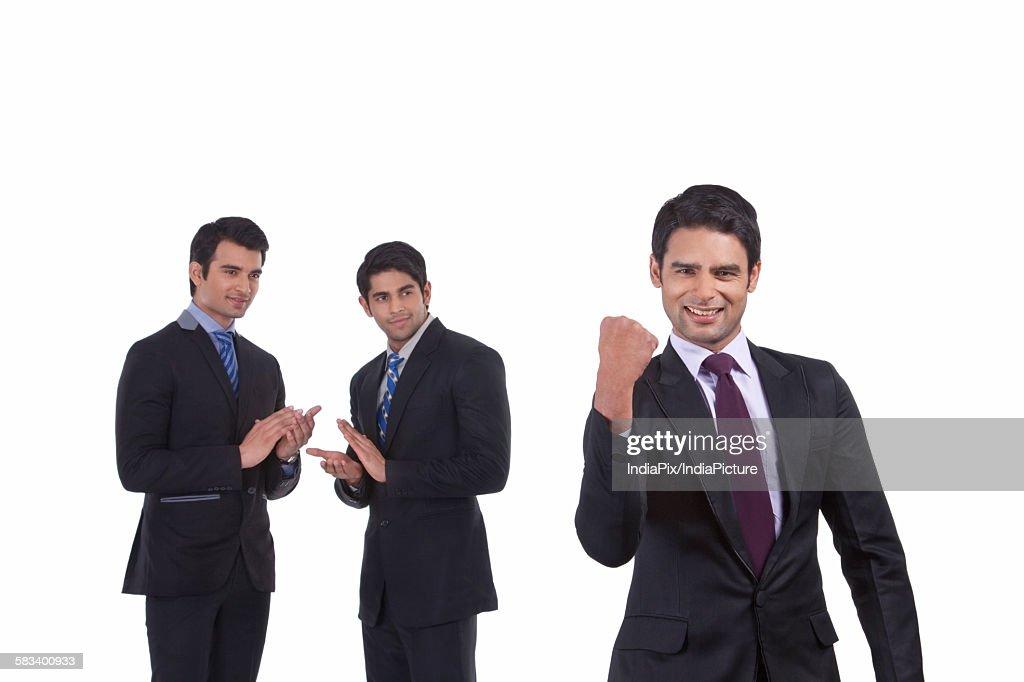 Colleagues clap as fellow businessman rejoices : Stock Photo