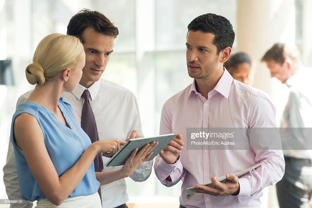 Colleagues collaborating using digital tablet : Stock Photo