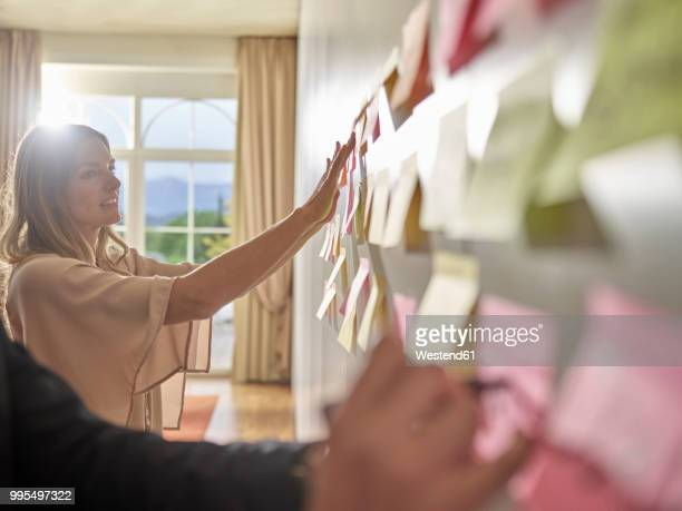 colleagues collecting ideas on sticky notes at the wall - hoarding concept stock pictures, royalty-free photos & images