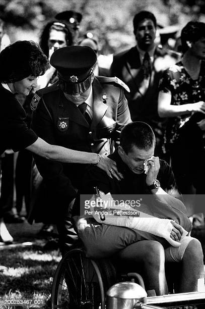 Colleagues comfort an injured police officer during a funeral service for a killed police officer in Johannesburg, South Africa