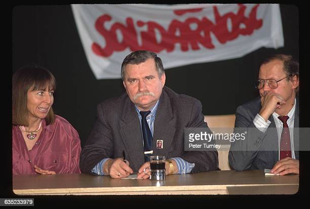 Colleagues confer with Lech Walesa in front of a banner reading Solidarnosc the name of the first independent trade union in Poland formed in 1980...