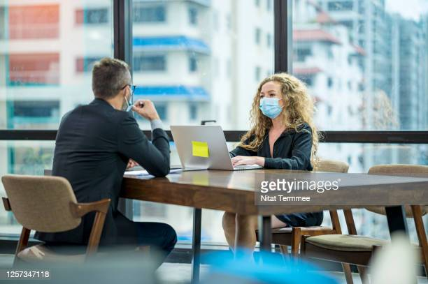 colleagues decision together in the skyscraper office. they are wearing medical face mask during spread of virus. - business finance and industry stock pictures, royalty-free photos & images