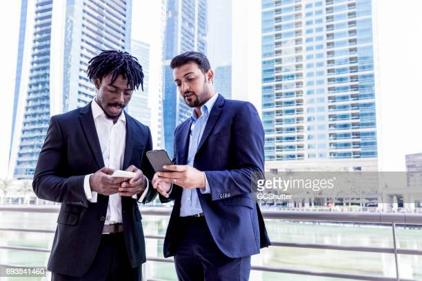 Colleagues discussing a business proposal using a smart phone