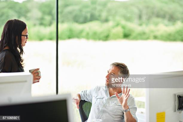 Colleagues discussing a project in modern office