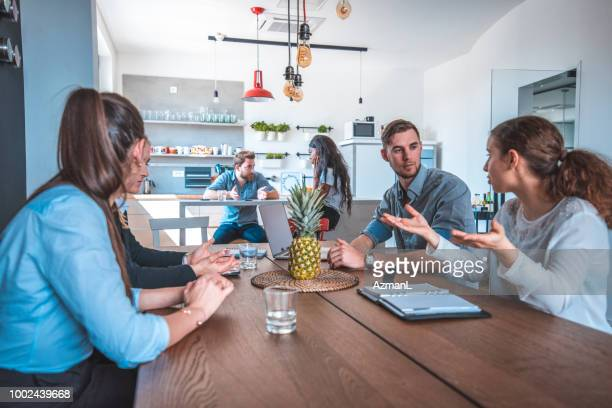 Colleagues discussing at table in cafeteria