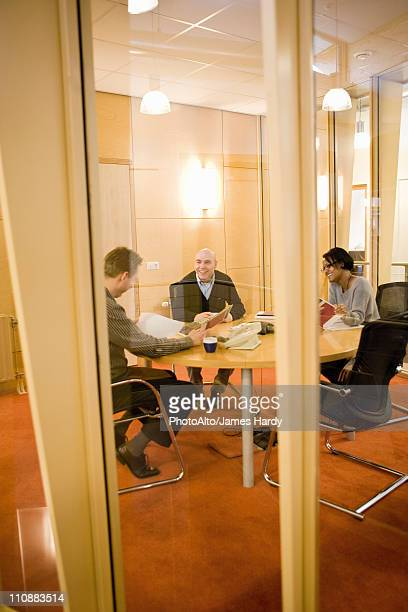 Colleagues discussing carpet samples in meeting room