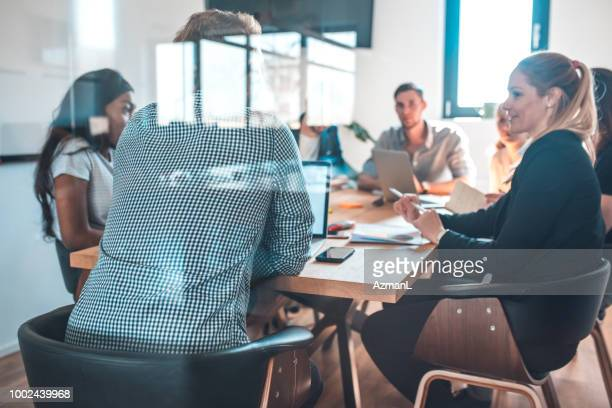 Colleagues discussing during meeting in office