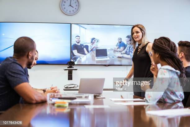 colleagues discussing during video conference in meeting room - virtual meeting stock pictures, royalty-free photos & images