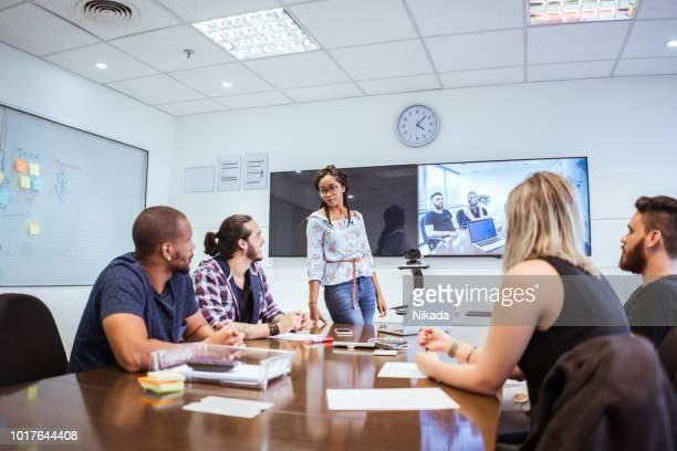 Kolleginnen und Kollegen diskutieren während der Videokonferenz im Tagungsraum