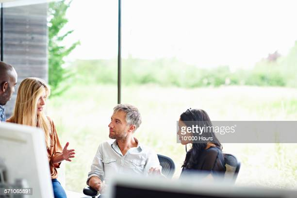colleagues discussing ideas in a modern office - sustainability stock photos and pictures